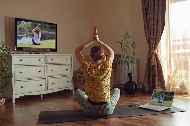 Спортивная молодая женщина берет уроки йоги онлайн и практикует дома во время карантина. концепция здорового образа жизни, благополучия, безопасности во время пандемии коронавируса, поиск нового хобби.