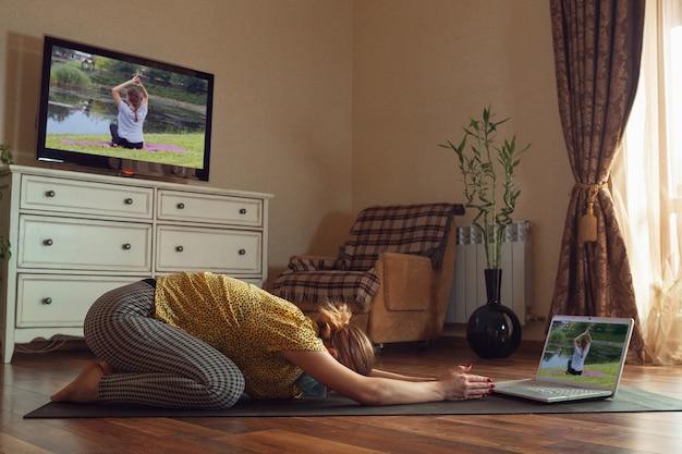 オンラインでヨガのレッスンを受け、検疫しながら自宅で練習するスポーティな若い女性。健康的なライフスタイル、ウェルネス、コロナウイルスのパンデミックの間安全であり、新しい趣味を探しているという概念。