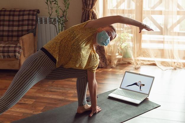 Спортивная молодая женщина берет уроки йоги онлайн и практикует дома во время карантина.