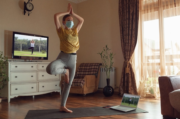 Sporty young woman taking yoga lessons online and practice at home while being quarantine. concept of healthy lifestyle, wellness, being safe while coronavirus pandemic, looking for new hobby.