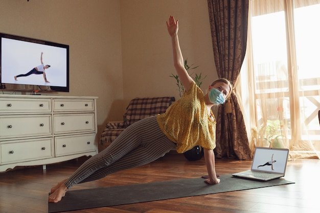 Sporty young woman taking yoga lessons online and practice at home while being quarantine.