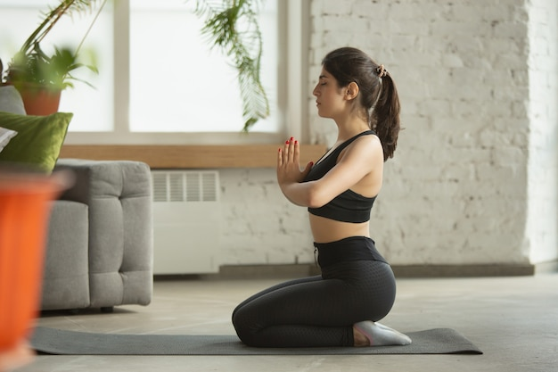Sporty young woman taking yoga lessons online and practices at home
