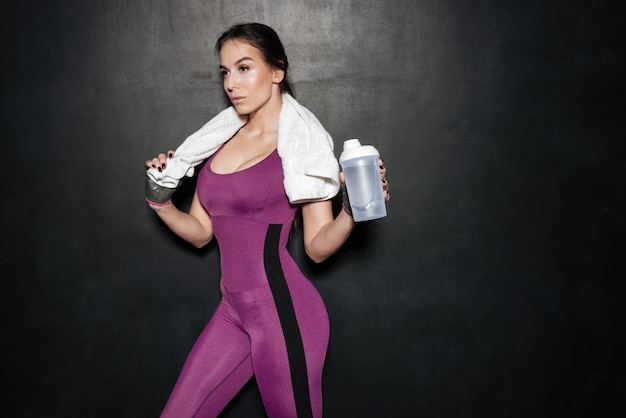 Sporty young woman in tracksuit with towel and water bottle