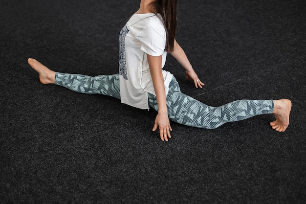 Sporty young woman trainer warms up muscles before training. girl sits on a twine. yoga or stretching is a healthy sports lifestyle. close-up.