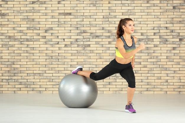 Спортивная молодая женщина тренируется дома