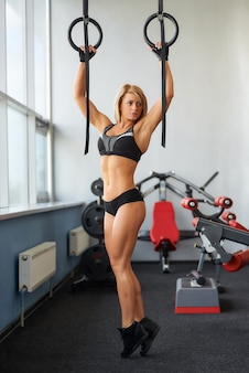 A sporty young woman who wears black tight shorts and a tank top is pulling herself up on gymnastic rings. a fitness blond girl is doing back workout in a gym.