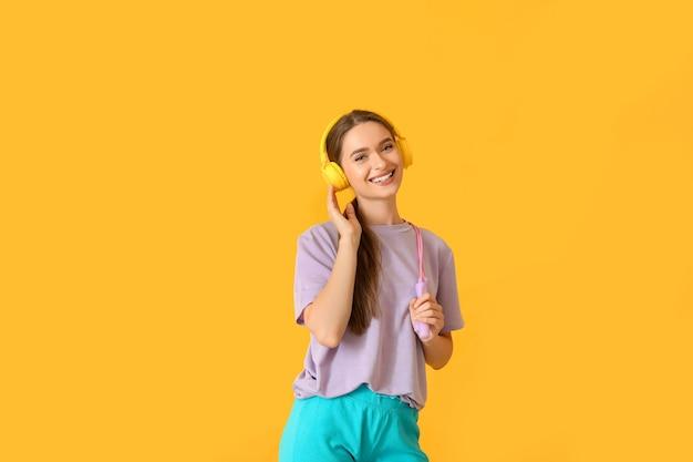 Спортивная молодая женщина с наушниками и прыжки через скакалку на цветном фоне