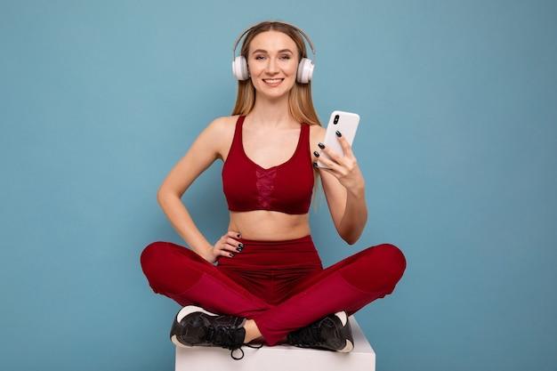 青い背景に座っているヘッドフォンと電話を持つスポーティな若い女性