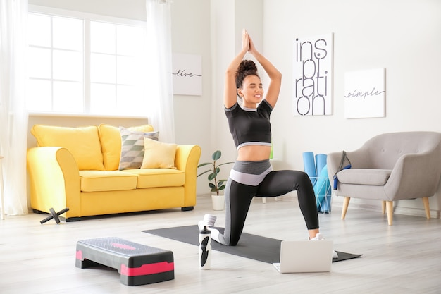 Sporty young woman with laptop training at home