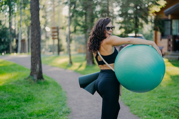 Sporty young woman working out outdoors with ball