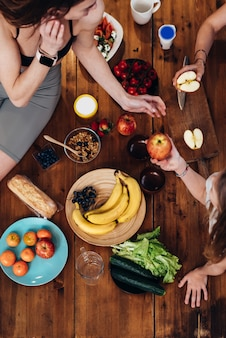 果物や野菜と台所のテーブルでスポーティな若い女性。