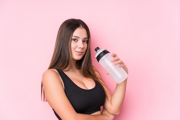 Молодая кавказская sporty женщина держа бутылку с водой