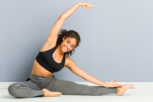 Йога молодой афро-американской sporty женщины сидя практикуя