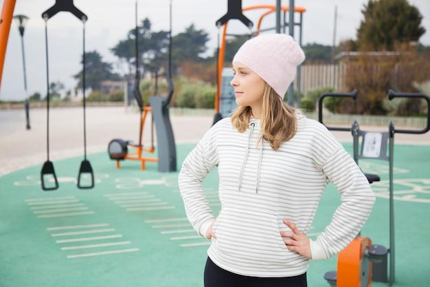 Задумчивый sporty женщина готова для тренировки на открытом воздухе