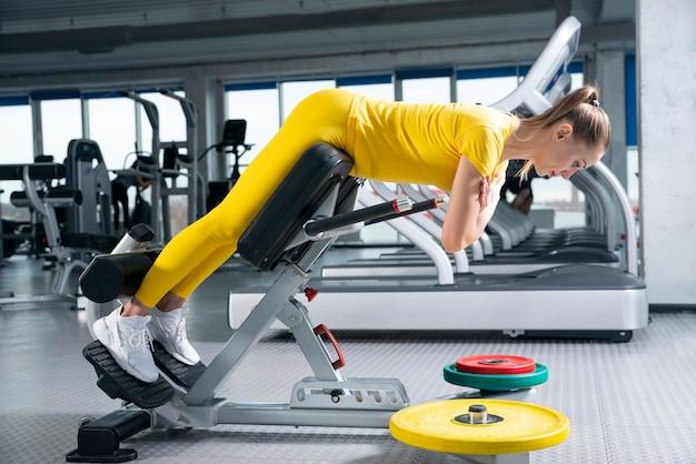 Молодая sporty разминка женщины на машине тренировок в спортзале