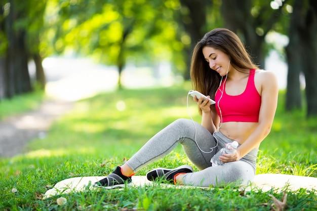 Молодая sporty женщина отдыхая в парке после тренировки и использования телефона.