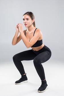 Sporty атлетическая женщина сидя на корточках делая приседания в спортзале изолированном над белой стеной