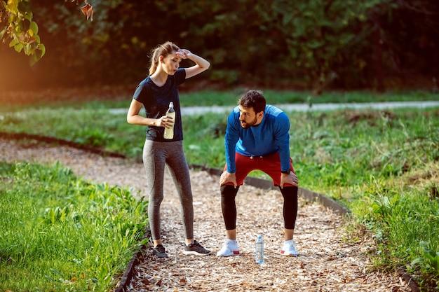 Утомленные кавказские sporty пары стоя на следе в древесинах и отдыхая от бежать. женщина держит бутылку с освежением. оба в спортивной одежде.