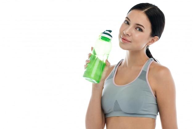 Усмехаясь sporty женщина стоя и держа бутылка воды изолированная на белой стене. концепция фитнеса и образа жизни