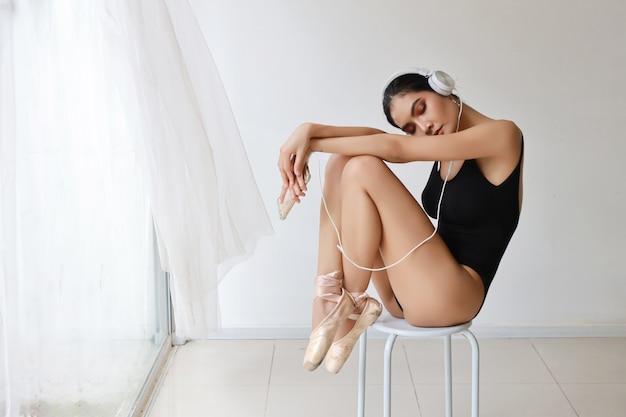 Sporty и здоровая молодая азиатская женщина с лицом красотки, практикуя балет с умным телефоном пока слушающ музыка от наушников