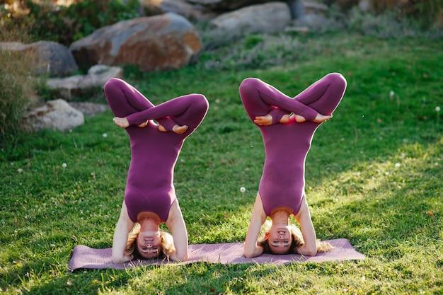 Группа в составе урок йоги sporty молодой женщины практикуя с инструктором, сидя в представлении лотоса. фокус камеры на вид сзади учителя.