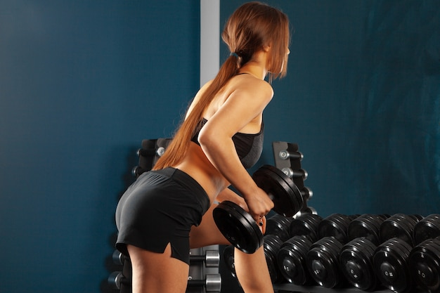 Молодая sporty тренировка женщины с гантелями спорт и бодибилдинг концепция