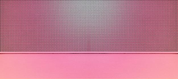 Точечная подсветка перфорированной металлической пластины розового цвета. металлический фон крупным планом