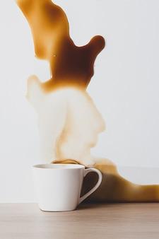 白いカップからこぼれたブラックコーヒーのスポット