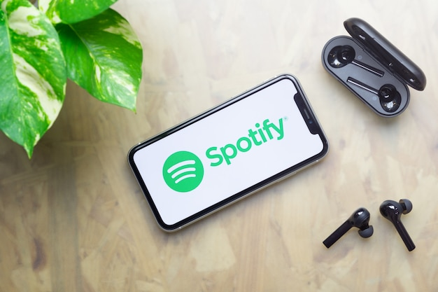 Логотип spotify на iphone с наушниками bluetooth