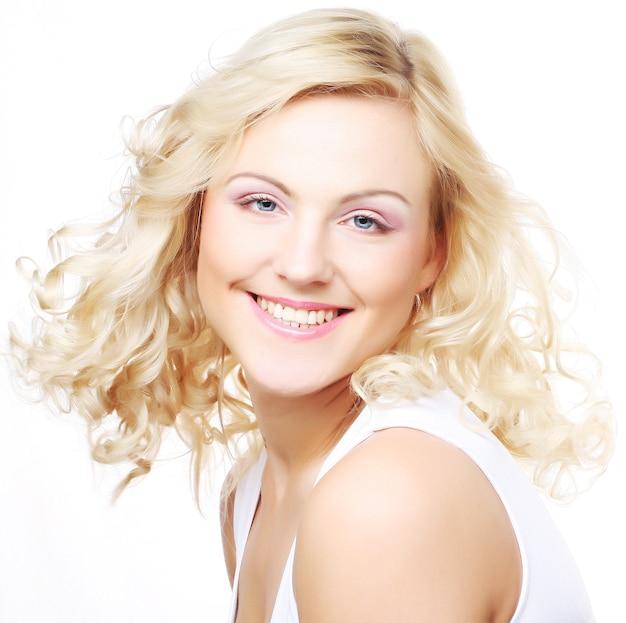 Безупречная молодая блондинка улыбается вам - изолированные на белом