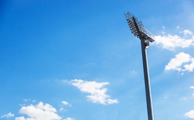 Spotlight on lighting tower of stadium on blue skye background