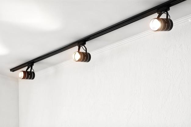 Точечные светильники под потолком на стене