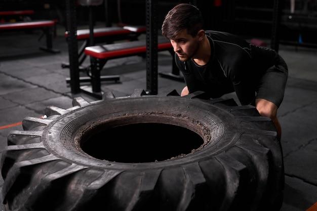 現代のフィットネスセンターで体力をつけるために引き抜かれたタイヤを押すスポットマン。スポーツウェアの男性は、クロスフィットとトレーニングに従事しています。スポーツ、健康的なライフスタイル、ボディービル、クロスフィット、トレーニングコンセプト