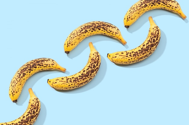 Spotted banana pattern on blue background. art food. copy space