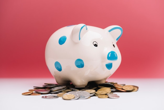 Spotted ceramic piggybank over coins in front of red background