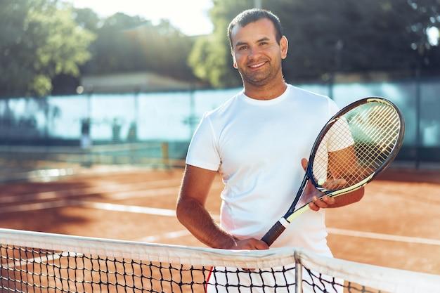 Человек с теннисной ракеткой стоит на грунтовом корте возле сетки