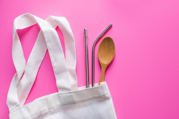 Плоская кладка устойчивых продуктов, spowooden и нержавеющей соломы в тканевой сумке на розовый