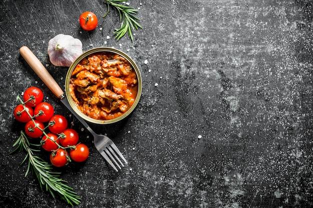 어두운 나무 테이블에 마늘, 체리 토마토, 로즈마리와 함께 깡통에 토마토 소스에 담근 sprat