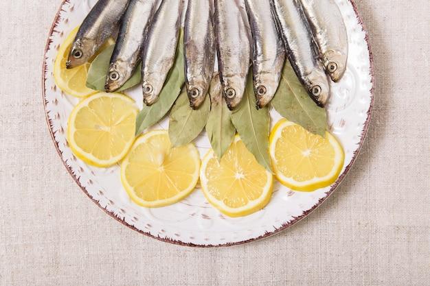 Килька на белой тарелке со специями и лимоном. грубая ткань. вид крупным планом