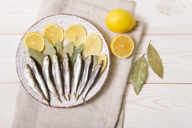 향신료와 레몬 흰색 접시에 sprat. 흰색 나무 배경, 거친 천. 평면도