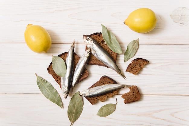 Килька на белой тарелке со специями и лимоном. белый деревянный фон. продовольственный фон.