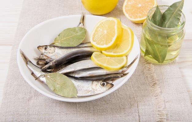 Килька со специями и лимоном, масло. белая тарелка. деревянный стол с грубой скатертью. вид крупным планом