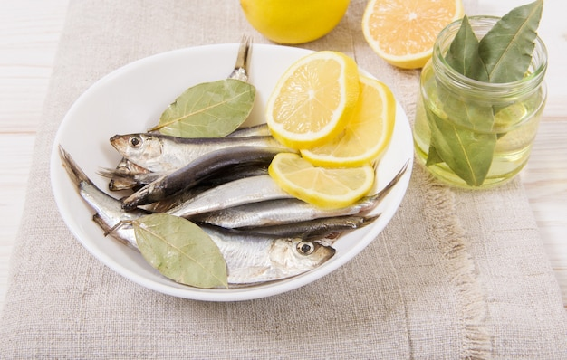 Sprat with spice and lemon,oil. white plate. wooden table with coarse tablecloth. close-up view