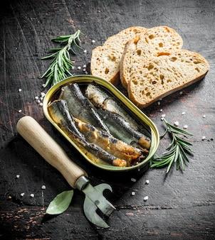 Шпроты в жестяной банке с нарезанным хлебом и розмарином. на темном деревенском