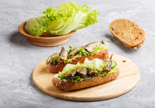 Sprats sandwiches with lettuce and cream cheese on wooden board on a gray concrete.