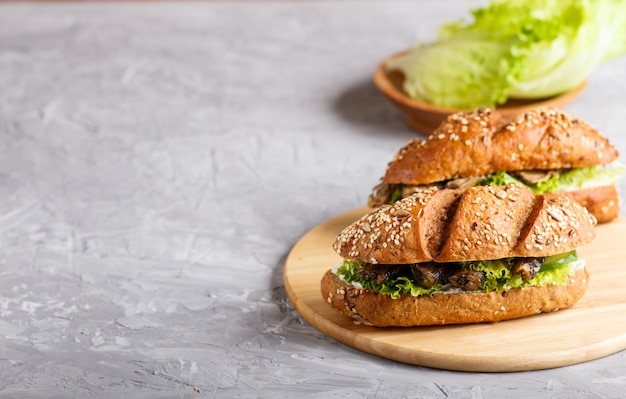 Sprats sandwiches with lettuce and cream cheese on wooden board