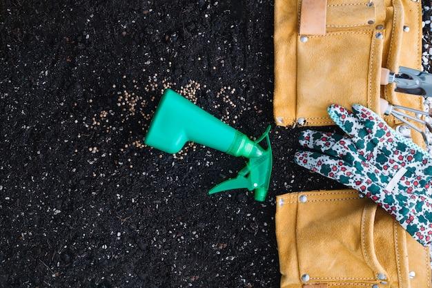 원예 도구가있는 가방 근처에 스프레이 병