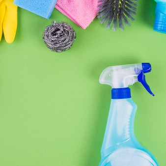 Spray bottle near cleaning equipments on green background