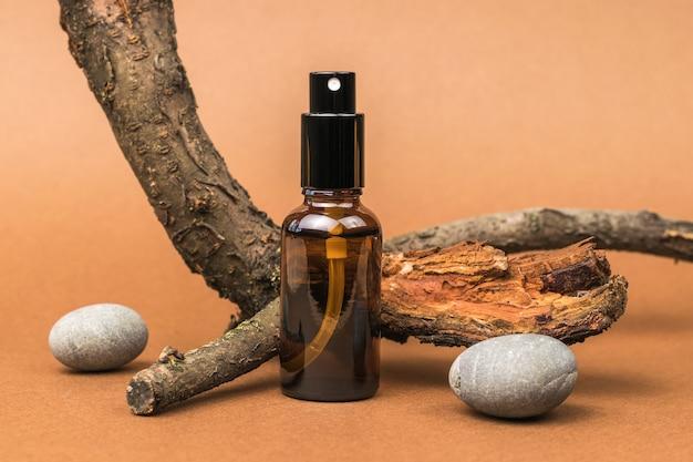 Бутылка с распылителем, старое дерево и камни на коричневом фоне. косметика и лекарственные препараты на основе природных минералов. концепция лечения и ухода за телом с использованием натуральных средств.