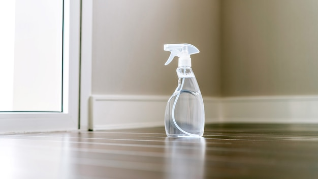 Spray bottle in a side view with a clear liquid inside on the wooden floor